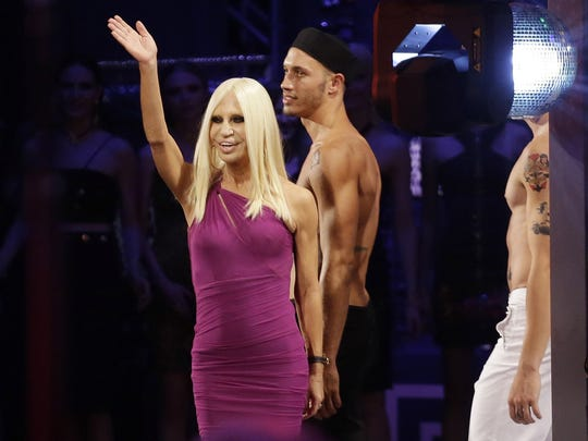 Italian designer Donatella Versace waves to the crowd