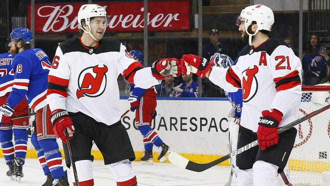Devils center Kevin Rooney, left, congratulates Kyle Palmieri after he scored in the March 7 game against the Rangers in New York. Rooney, a former PC player who became a free agent, signed a two-year contract with the Rangers last week.