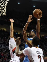 Denver Nuggets guard Emmanuel Mudiay drives to the basket on Portland Trail Blazers guard Brian Roberts, left, and forward Noah Vonleh (21) during the first quarter of an NBA basketball game in Portland, Ore., Wednesday, April 13, 2016. (AP Photo/Steve Dykes)