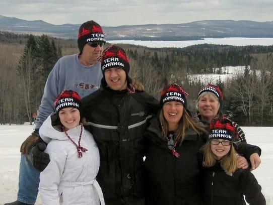 """The Romanow family wears hat reading """"Team Romanow."""""""