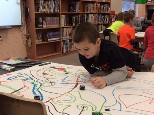 Colorful marker lines serve as directions for robots in this kindergarten project.