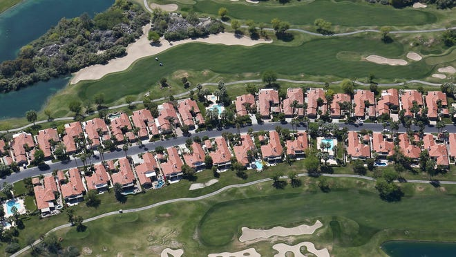 Houses are surrounded by grass and water features in this neighborhood in south La Quinta.