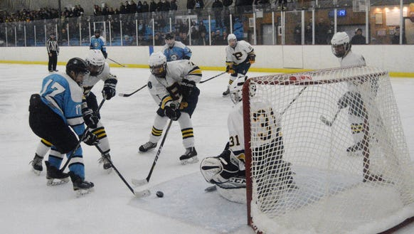 Suffern forward Evan  Cama (17) battles for a puck