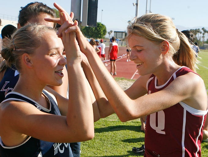 Megan Huebner  (right) of La Quinta High School track celebrates her Desert Valley League cross country victory with a teammate. Huebner won with a time of 18.43 September 22, 2010. Wade Byars, The Desert Sun
