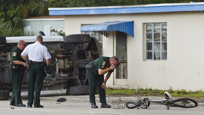 Lee County Sheriff's Officers inspect the scene of a crash involving an SUV and a bicyclist Monday afternoon in North Fort Myers on North Tamiami Trail near East Mariana Ave.