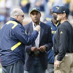 Michigan interim athletic director Jim Hackett, left, talks with former U-M quarterback Dennis Franklin and football coach Jim Harbaugh, right, during warm-ups Sept. 26, 2015, in Ann Arbor.