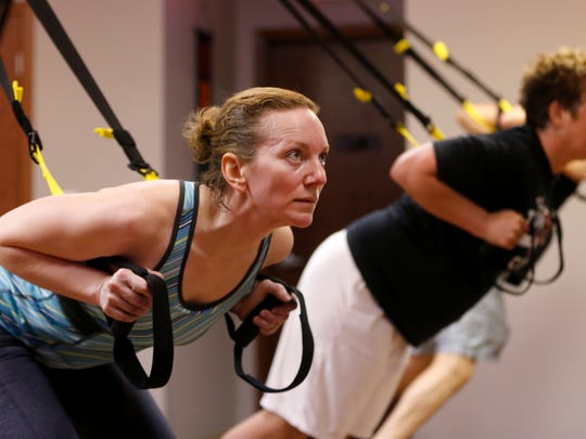 Jyl Wonnell [cq], left, of Cambridge exercises with TRX bands during a class at Cycle Down Dawg in West Des Moines.