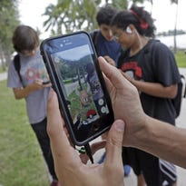 """In this July 12, 2016, photo, Pinsir, a Pokemon, is found by a group of Pokemon Go players at Bayfront Park in downtown Miami. The """"Pokemon Go"""" craze has sent legions of players hiking around cities and battling with """"pocket monsters"""" on their smartphones."""