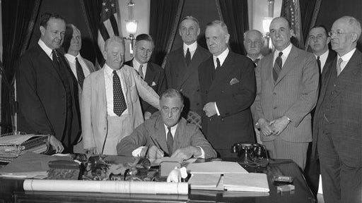 President Franklin D. Roosevelt signs the Banking Bill at the White House on June 16, 1933, surrounded by sponsors of the measure. From left, Sen. A.W. Barkley of Kentucky; Thomas P. Gore of Oklahoma; Carter Glass of Virginia; J.F.T. O'Connor, comptroller of currency; Sen. William G. McAdoo; Rep Henry B. Steagall of Alabama; Sen. D.U. Fletcher of Florida; and Rep. T. Alan Goldsborough of Maryland.