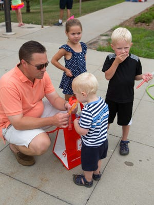 Brian Scott of Urbandale sits with his kids (from left) Ava Scott, 5, Ellis Scott, 2, and Gabe Scott, 5, as they eat popsicles Tuesday, Aug. 5, 2014, during National Night Out at the Urbandale Police Department in Urbandale.