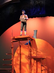 """James (Carl Kimbrough) sings from atop a giant peach in this rehearsal scene from Abilene Christian University's """"James and the Giant Peach,"""" which opens a two-weekend run Friday."""