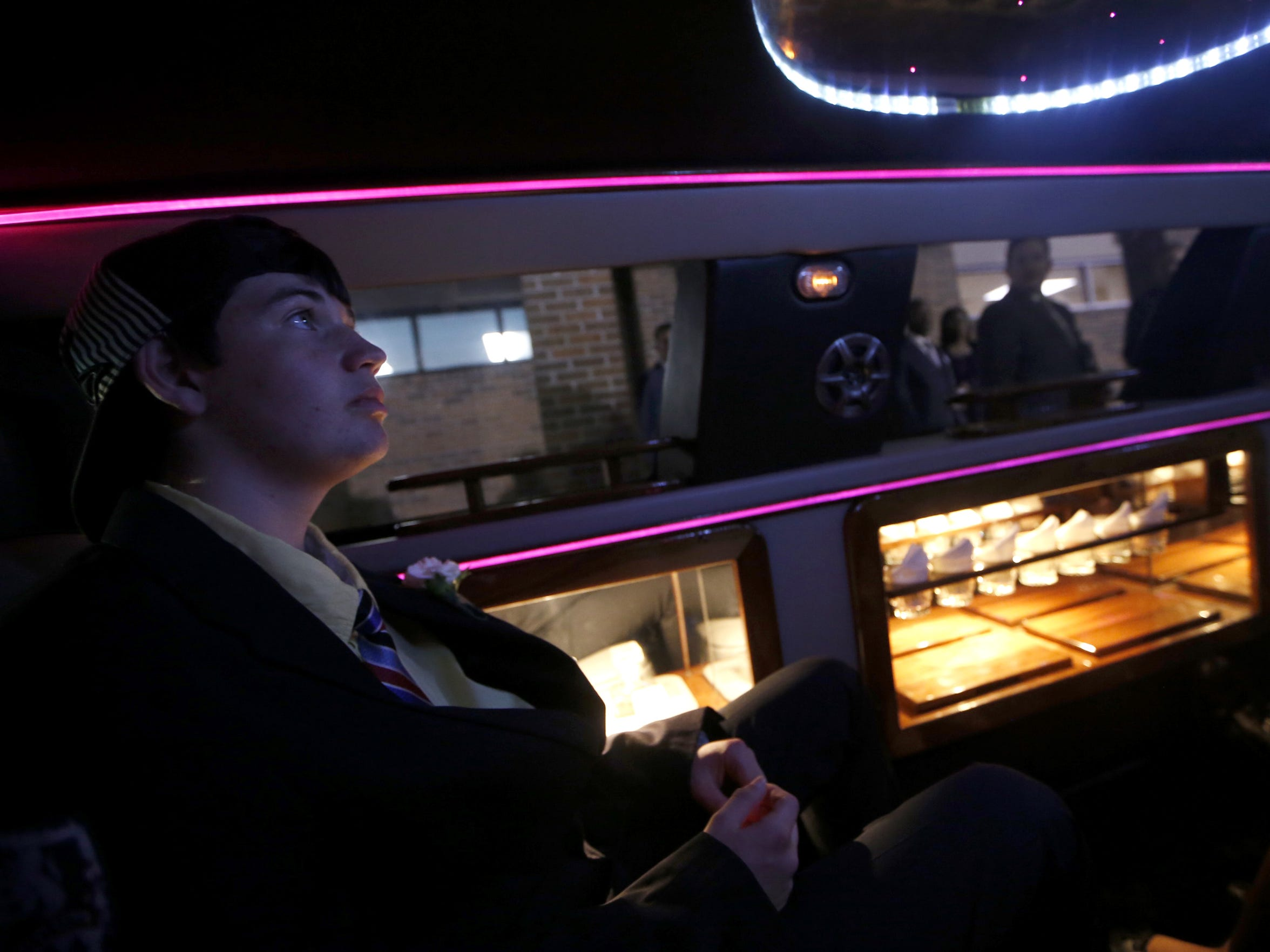 Charlie Harrison, 17, looks into the lights of the limo as it takes guests for a joyride during the Night to Shine special needs prom at Genesis Church on Friday, Feb. 12, 2016.