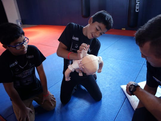 Metro Elementary School of Design Ayden Tober, 11 (from left), and Rudy Herrera, 11, learn infant CPR with the help of Corpus Christi Fire Department Cadet Erik Buys at Del Mar College West on May 23, 2017. Students in the BullyProof program at the school, the CPR and first aid training gave them a chance to work as a team, skills they learned throughout the weeks they spent in the program.