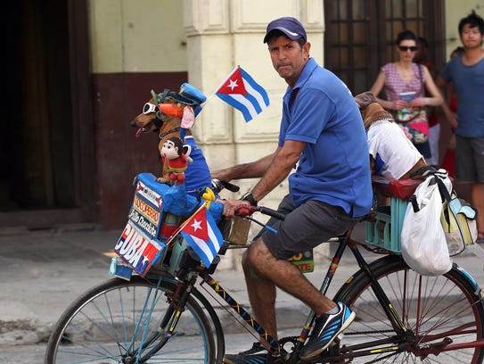A man on a bicycle rides along with his dog in Havana,