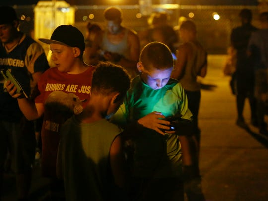 """Pokemon Go"" players Brady Sammons, 13, of Elsmere (left) and Shawn Brown, 12, of Richardson Park, gather adjacent to New Castle's Battery Park after dark Tuesday. Fans also have descended on places like the Wilmington Riverfront and University of Delaware campus to catch monsters."