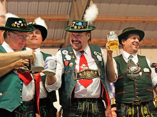 Dale Blant ( second from right) and members of The Freistadt alte Kameraden Band bump their steins together in a celebratory manner after performing during Oktoberfest, at the former Bavarian Inn.