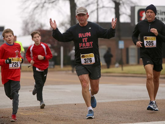 Jeff Keas gestures as he runs during the 12th annual Turkey Day 5K in Jackson, Tenn., on Thursday, Nov. 24, 2016.