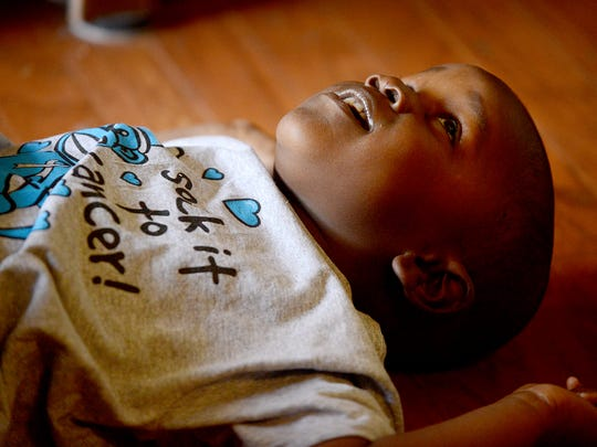 Kyson Thomas, wearing his 'sock it to cancer' T-shirt, looks up at his parents from the floor during an interview Friday morning. A tumor was removed from Kyson's brainstem by doctors at St. Jude Children's Research Hospital.