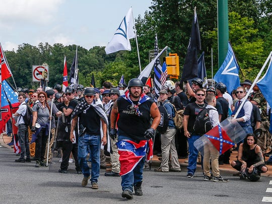 Multiple white nationalist groups march to McIntire Park in Charlottesville, Va., on Aug. 12. In the center background is a black-and-white American flag with a thin blue line across its center.