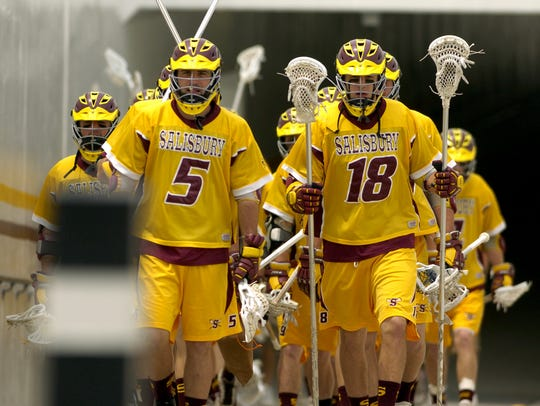 (From left) Seniors Mike Edwards and Kyle Hartzell lead Salisbury University's men's lacrosse team out of the tunnel, as they make their way to the field.