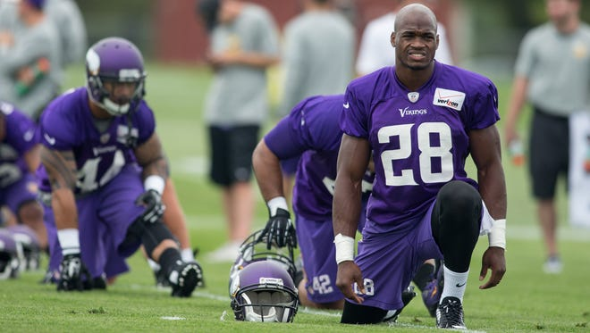 Vikings running back Adrian Peterson (28) stretches at training camp.