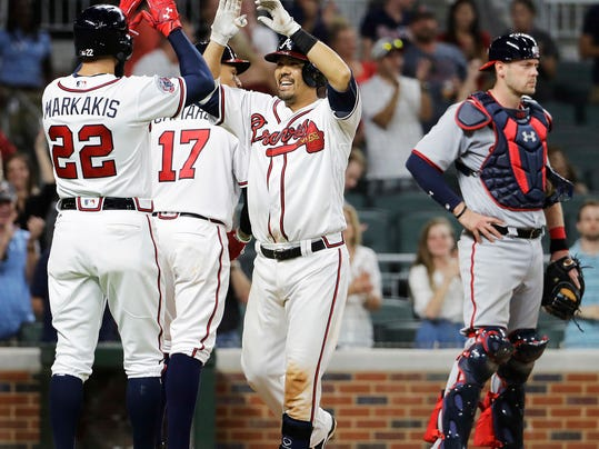 Atlanta Braves' Kurt Suzuki, center, high-fives teammate Nick Markakis after they scored off Suzuki's two-run home run as Washington Nationals catcher Matt Wieters, right, stands by in the eighth inning of a baseball game in Atlanta, Friday, May 19, 2017. (AP Photo/David Goldman)