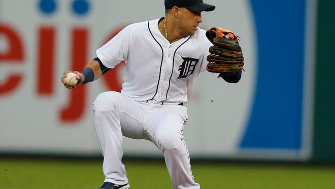 Tigers shortstop Jose Iglesias loses he balance spinning around trying to throw out Angels second baseman Grant Green at first base in the second inning at Comerica Park.