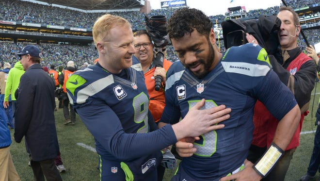 Seattle Seahawks punter Jon Ryan (9) and quarterback Russell Wilson (3) celebrate following the overtime victory over the Green Bay Packers in the NFC Championship Game at CenturyLink Field.
