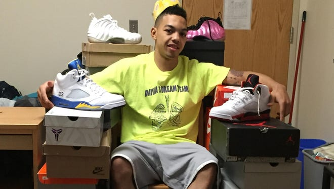 Monmouth University sophomore point guard Justin Robinson shows off part of his sneaker collection, which he says is at 52 pairs