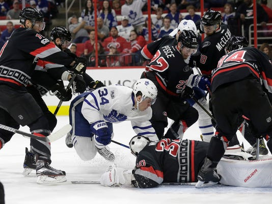 Toronto Maple Leafs' Auston Matthews (34) falls in front of Carolina Hurricanes goalie Cam Ward during the first period of an NHL hockey game in Raleigh, N.C., Sunday, Feb. 19, 2017. (AP Photo/Gerry Broome)