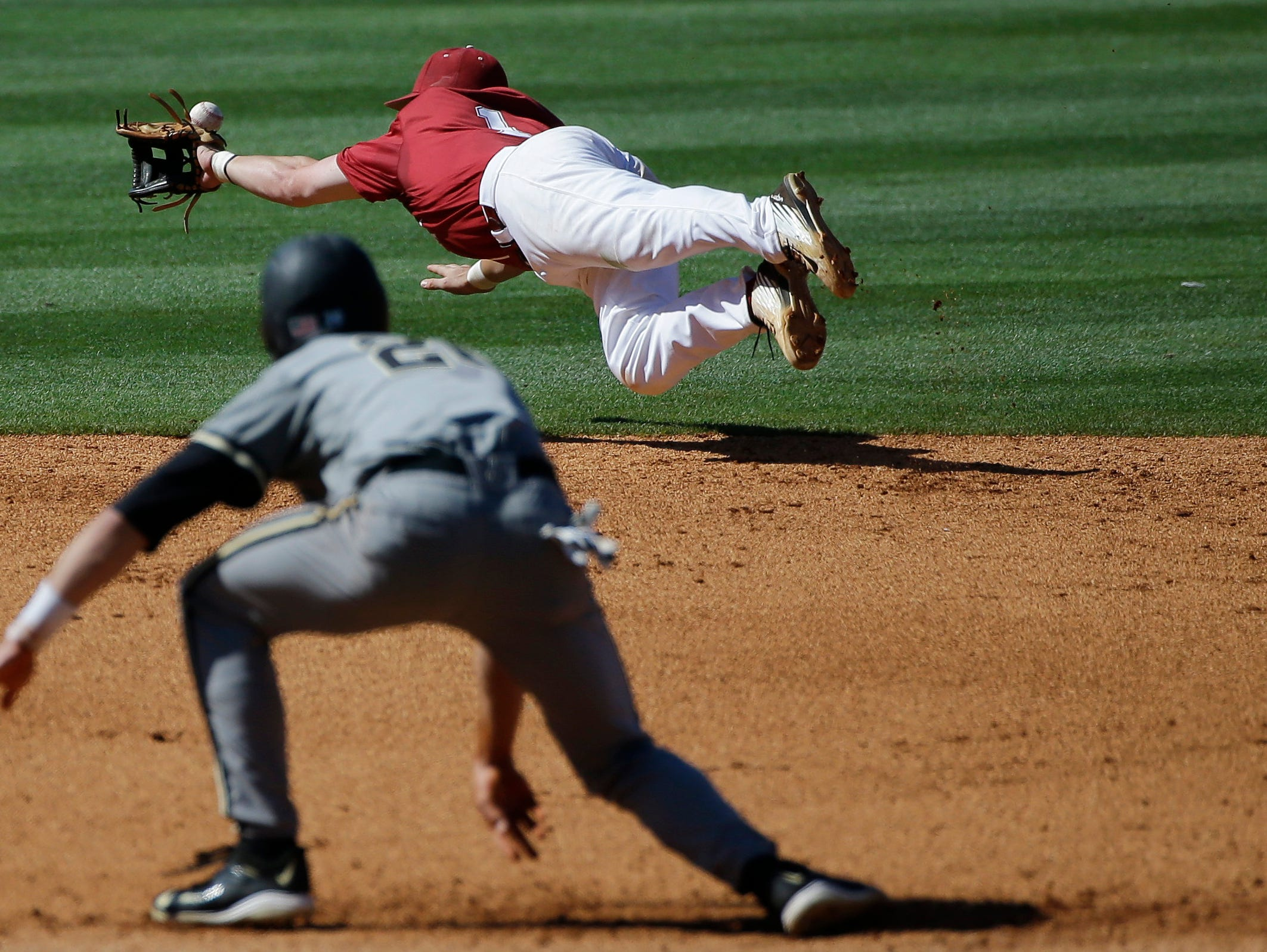 Alabama's Mikey White, top, dives for the ball and but misses it as Vanderbilt Bryan Reynolds rounds second base headed for third during the fourth inning of a Southeastern Conference Tournament game Friday in Hoover.