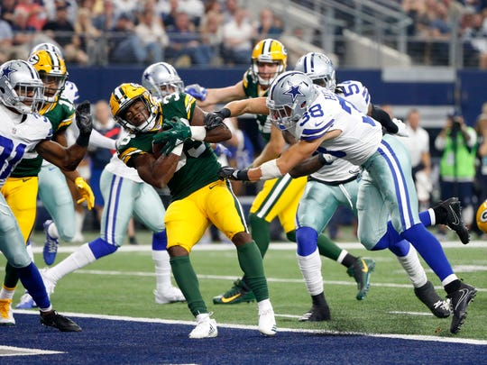 Green Bay Packers running back Aaron Jones (33) gets past Dallas Cowboys safety Jeff Heath (38) as Jones runs the ball for a touchdown in the first half of an NFL football game Oct. 8 in Arlington.