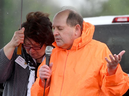 Pastor Bonnie Peltomaa holds an umbrella for Pastor Vaughn Loose of First Church of the Brethren as the two pray Thursday afternoon during the National Day of Prayer in the parking lot of the Ashland Road Big Lots.