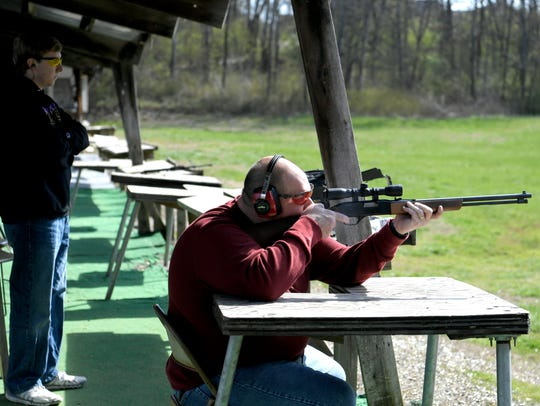 Scott Hensley and his son, Austin, shoot at targets
