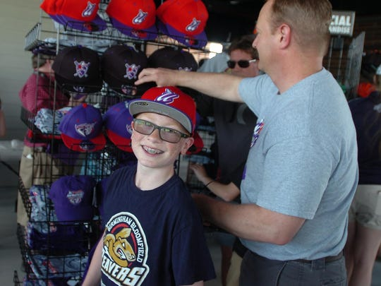 Eric Berg from Utica and his dad, Steve, take a look at hats at the new stadium.