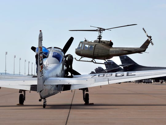 A Huey helicopter flies past an AD Skyraider as the crew secure the airplane at last year's air show at Dyess Air Force Base.