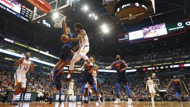 Phoenix Suns forward Josh Jackson (20) passes the ball off around Oklahoma City Thunder forward Josh Huestis (34) during the second quarter at Talking Stick Resort Arena in Phoenix January 7, 2018.