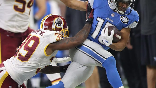 Lions wide receiver Golden Tate is tackled by the Washington Redskins' Donte Whitner.