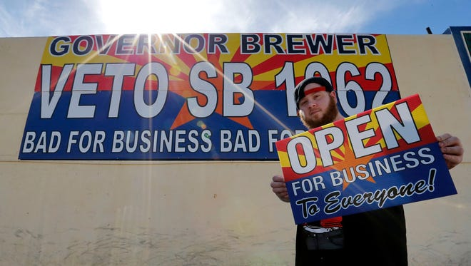 """Josh Deinert, a graphic designer, shows a sign that reads """"Open for business to everyone"""" on Wednesday in Phoenix."""