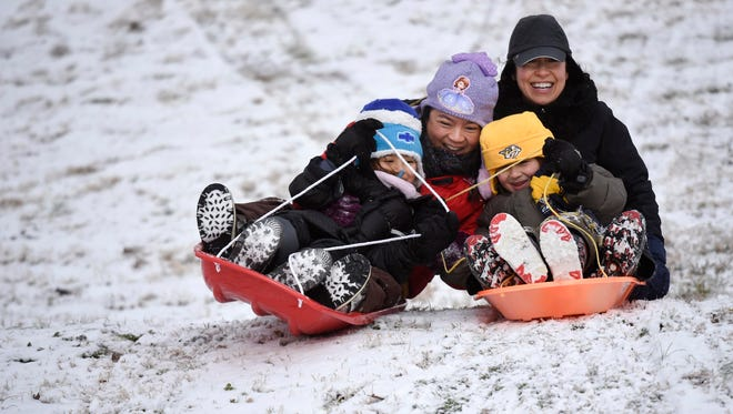 Anh Meadows and her daughter Sophia, left, collide with Joan Popkin and Noah Kuehn as they slide down a hill at West End Junior High School in Nashville, Tenn., Saturday, Jan. 13, 2018.
