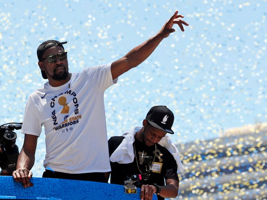 Golden State Warriors' Kevin Durant waves to fans during the team's NBA basketball championship parade, Tuesday, June 12, 2018, in Oakland, Calif. (AP Photo/Tony Avelar)