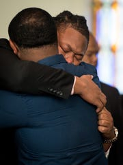 D'Andre Litaker, right, hugs his uncle Ashley Coleman,