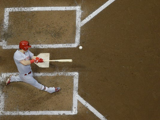 Cincinnati Reds' Scooter Gennett hits a two-run scoring single during the third inning of a baseball game against the Milwaukee Brewers Friday, Aug. 11, 2017, in Milwaukee. (AP Photo/Morry Gash)