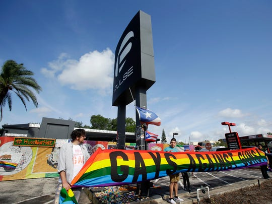 Activists hold a banner in front of the Pulse nightclub site after a news conference, Thursday, May 4, 2017, in Orlando, Fla. The owner of the Pulse nightclub said the site will become a memorial and a museum to honor the 49 people who were killed and the dozens more who were injured during the worst mass shooting in modern U.S. history. (AP Photo/John Raoux)