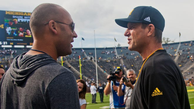 Former New York Yankees shortstop Derek Jeter, left, shakes hands with Michigan football coach Jim Harbaugh before a game against BYU in Ann Arbor on Sept. 26, 2015.