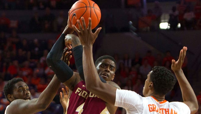 Florida State  guard Dwayne Bacon attempts to pass the ball while being defended against Clemson.