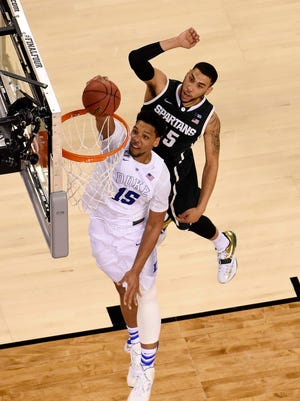 Duke Blue Devils center Jahlil Okafor (15) dunks the ball against Michigan State Spartans guard Denzel Valentine (45) during the second half of the 2015 NCAA Men's Division I Championship semi-final game at Lucas Oil Stadium in Indianapolis on April 4, 2015.