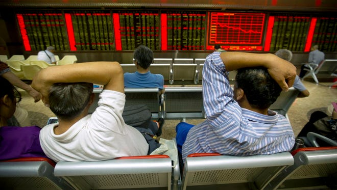 Investors monitor displays stock information at a brokerage house in Beijing on July 15, 2015.