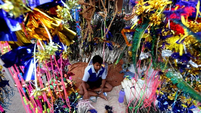 A child sits in a shop selling decorative items for cattle, ahead of the Govardhan Puja in Bhopal, India, on Nov. 7. Govardhan Puja is celebrated the day after the Diwali, the Hindu festival of lights.