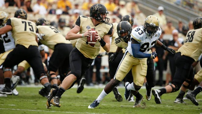 Vanderbilt quarterback Kyle Shurmur (14) rolls out of the pocket and is pursued by Georgia Tech defensive lineman Antonio Simmons (93) on Sept. 17, 2016.
